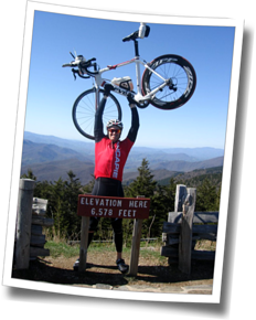 DZ Athlete holding his bike overhead in victory at the summit of Mt. Mitchell, at DZ Asheville Spring Triathlon Training Camp 2012