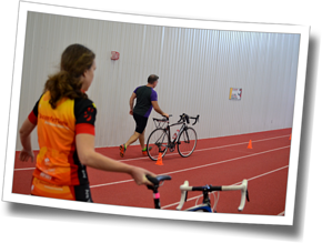 Athletes practice maneuvering the bike around a cone course indoors at the Gryphon's Fieldhouse, simulating a crowded T2 triathlon transition, DZ Winter Triathlon Clinic - Guelph, 2014