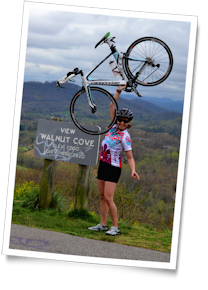 Michelle holds her bike aloft for her cycling hero shot at the Walnut Cove overlook, Blue Ridge Parkway, North Carolina